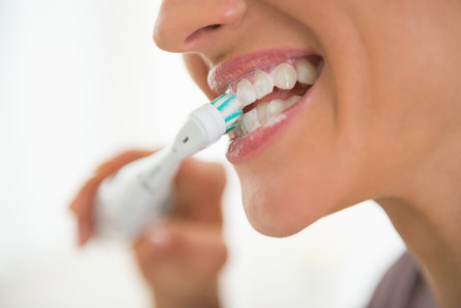 Closeup On Young Woman Brushing Teeth With Electronic Toothbrush