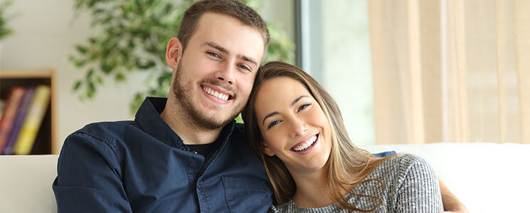 Photograph of a happy, smiling male & female couple holding each other while sitting on a couch in a home setting.
